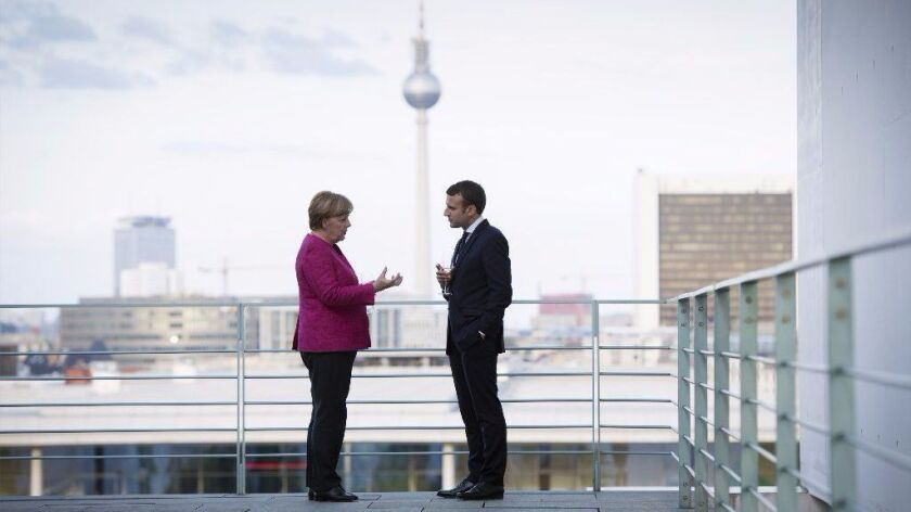 German Chancellor Angela Merkel talks with French President Emmanuel Macron in Berlin on Monday, in a photo provided by the German government.