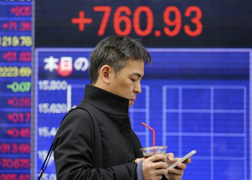 A man walks by an electronic stock board of a securities firm in Tokyo, Monday, Feb. 15, 2016. Tokyo's main share index, the Nikkei 225, jumped 4.4 percent to 15,615.84 in early trading Monday, helped by a weakening in the Japanese yen. (AP Photo/Koji Sasahara)
