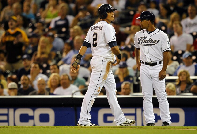 Padres coach Dave Roberts (right) moves from first base to the bench this season. K.C. Alfred • U-T file photos