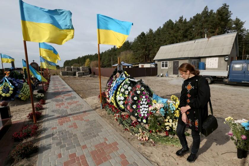 Anastasia Golota at the graveside of her husband, Oleksandr Markiv, at the cemetery in Obukhiv, Ukraine.