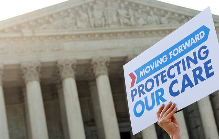 A supporter of the Affordable Care Act demonstrates outside the Supreme Court building this year. President Obama's reelection all but brings an end to Republican efforts to upend the law.