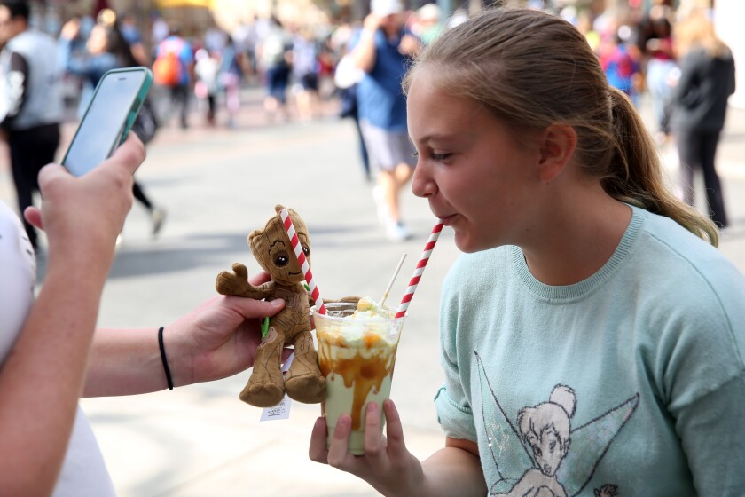 ANAHEIM, CA-OCTOBER 9, 2019: Millie Kattenhorn, left, takes a picture of daughter Katie Kattenhorn, 10, eating a Carmel Apple Smoothie to post to social media at Disney California Adventure Park on October 9, 2019 in Anaheim, California. Disneyland, and other theme parks, are creating visually interesting Halloween inspired foods with the idea that park goers might want to post them to social media. (Photo By Dania Maxwell / Los Angeles Times)