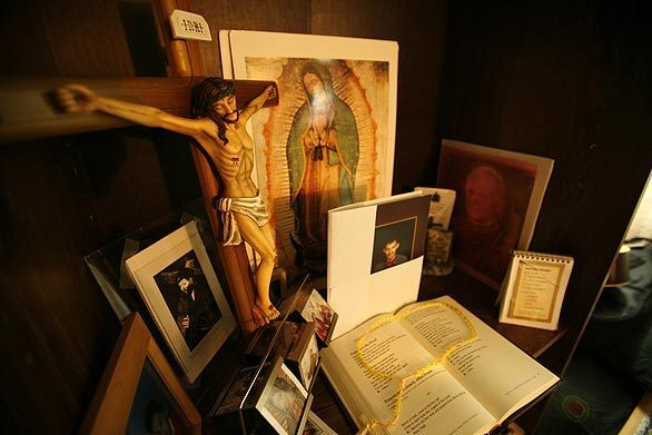 Rafael and Maria Alarcon have set up a shrine with photographs, a prayer book, rosary and Christian icons in the bedroom of their son's room in their Pasadena home Wednesday. Jorge Alarcon, who had been diagnosed schizophrenic, was found dead after an apparent suicide Monday in a county-run mental hospital.