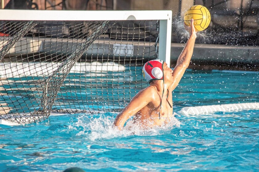 Poway High's goalie reaches up to block the ball during a water polo game.
