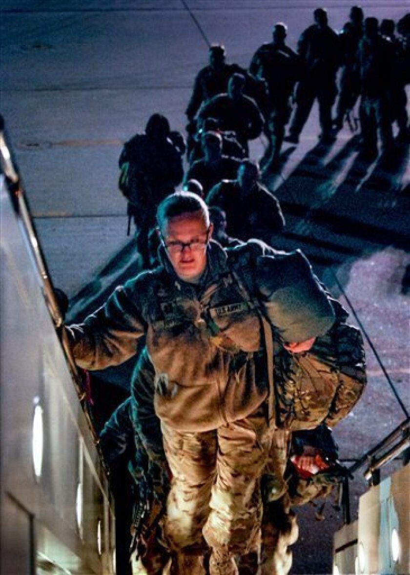 Troops with the 101st Airborne Division at Fort Campbell, Ky., board a plane on Wednesday, Feb. 20, 2013, to depart for a yearlong deployment to Afghanistan. The division is leaving for its third deployment in the last five years. (AP Photo/Kristin M. Hall)
