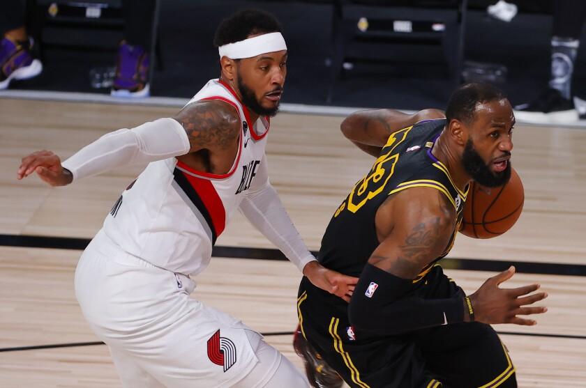 El jugador de los Lakers de Los Ángeles LeBron James (derecha), conduce la pelota ante su rival de los Trail Blazers.