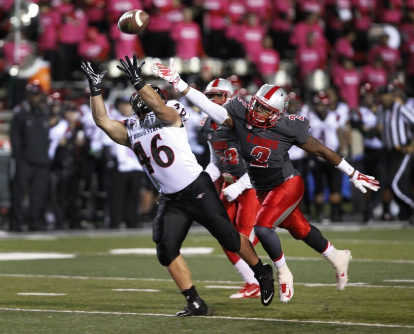 San Diego State's Dakota Gordon (46) attempts to catch an incomplete pass against New Mexico's Kimmie Carson during the first half of an NCAA college football game Friday, Oct. 10, 2014, in Albuquerque, N.M. (AP Photo/Eric Draper)