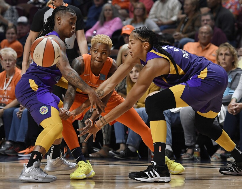 Connecticut Sun's Courtney Williams, center, passes between Sparks' Riquna Williams, left, and Candace Parker during the first half of Game 2 of a WNBA playoff game on  Thursday in Uncasville, Conn.