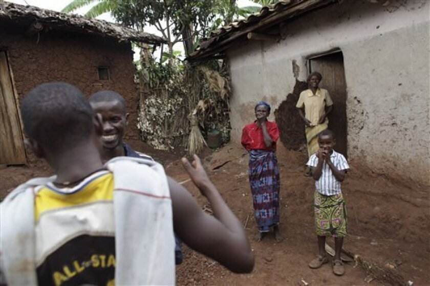 In this photo taken Sunday, Oct. 11, 2009, Elias Sanvura, 30, second left, is greeted by his younger brother Emmanuel Nzabandora, 17, as his mother Daphrose Nyiranzigiyeas, center, his older sister Laurence Uwizeyimana, top right, and a young relative look on in the village of Bukomuyu, outside Butare, Rwanda. Sanvura carried his little brother, then 3, on his back for three months as the family fled to Congo in 1994. In an effort to weaken an atrophying rebel movement that has terrorized eastern Congo for 15 years, U.N. peacekeepers are waging a campaign to persuade more and more of the rank and file militiamen to lay down their weapons and return home. (AP Photo/Rebecca Blackwell)