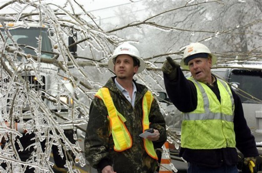 Southwestern Electric Power Company worker Sam Collier, right, and Kyle Pemberton, left, discuss removing tree limbs from power lines in Fayetteville, Ark., Thursday, Jan. 29, 2009. Thousands in the city are still without electricity following an ice storm that hit the northwest Arkansas region Tuesday. (AP Photo/April L. Brown)