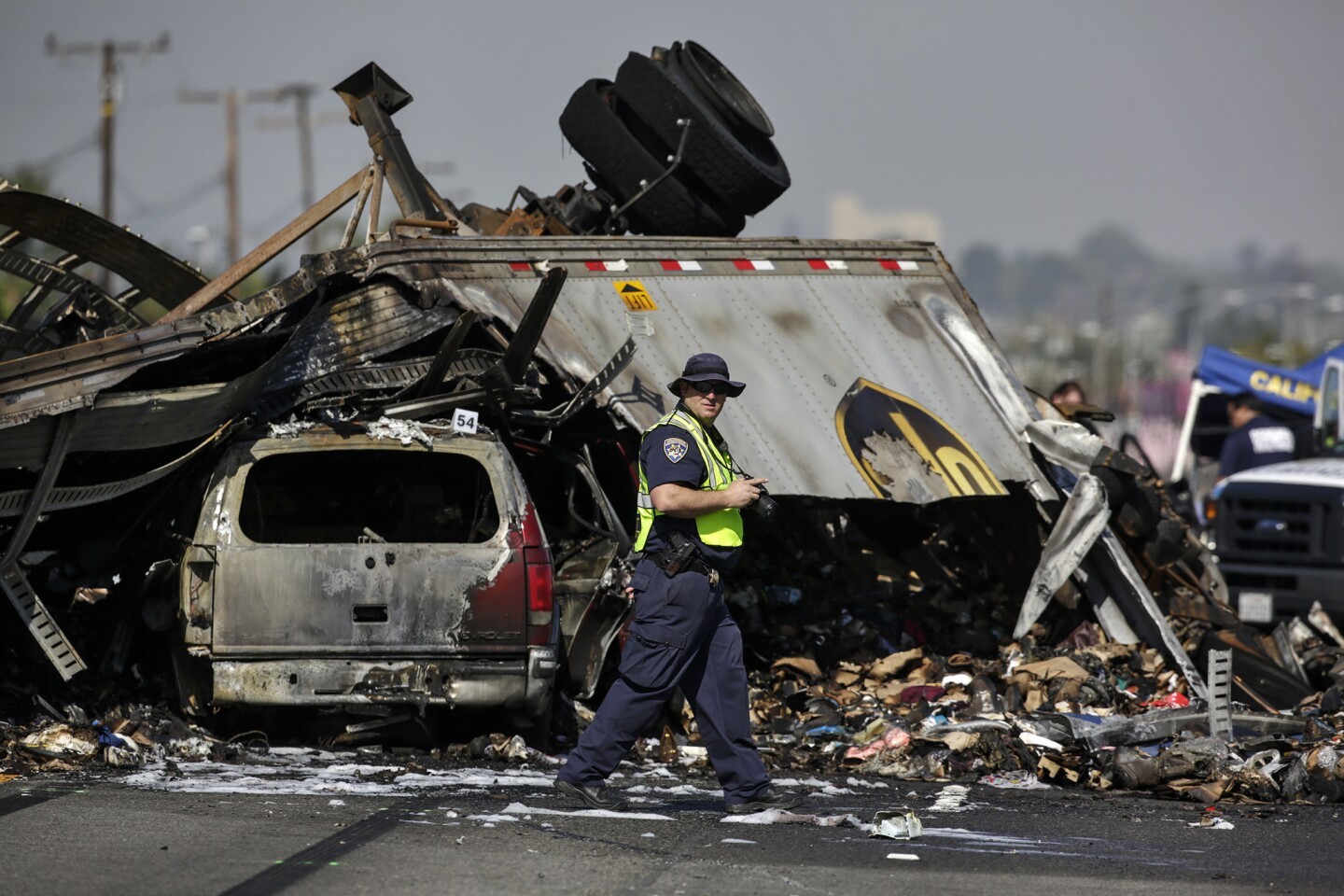 A California Highway Patrol investigator takes photographs at the scene of Saturday's multivehicle crash on the 5 Freeway in Commerce that killed three people.