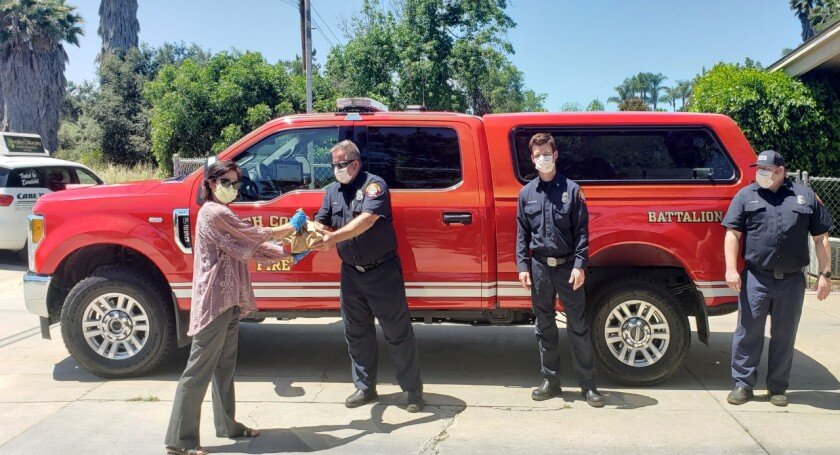 """The Foundation for Senior Care teamed up with Major Market in Fallbrook to donate """"thank you"""" lunches to first responders at stations in the Fallbrook/Rainbow/Bonsall area of the North County Fire Protection District. Madison Ohlson (left) delivers lunch to NCFPD's Station #2 at 2180 Winterwarm Drive, where firefighters Brent Itzaina, Joey Bradshaw and Rob Hager received lunch sacks for those on duty."""