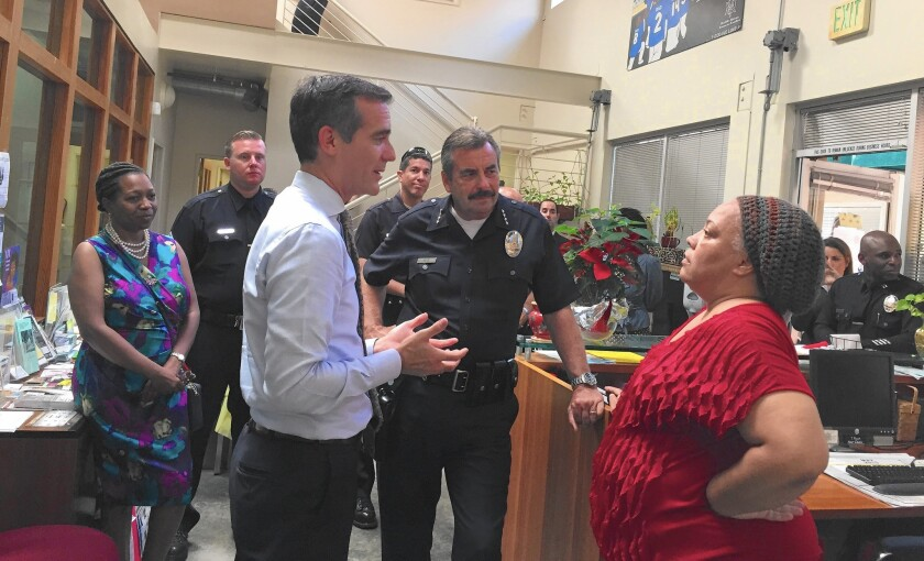 Mayor Eric Garcetti, left, and Police Chief Charlie Beck speak with Felica Jones, director of programs for Healthy African American Families II, during their visit to Leimert Park.