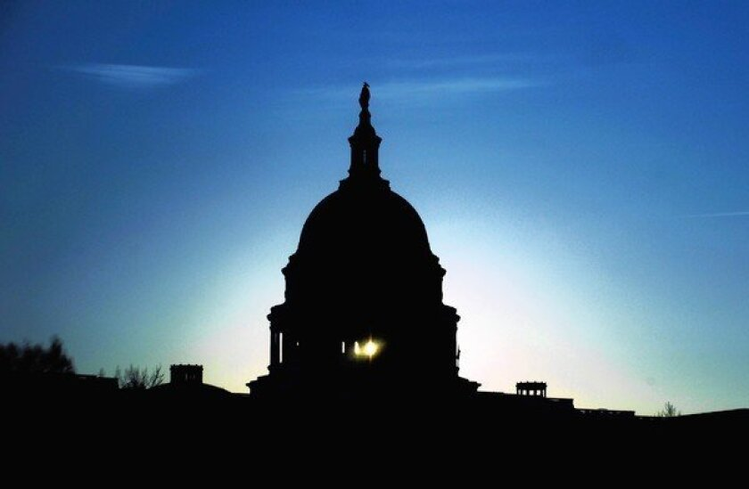 The Capitol dome in Washington silhouetted against a low sun