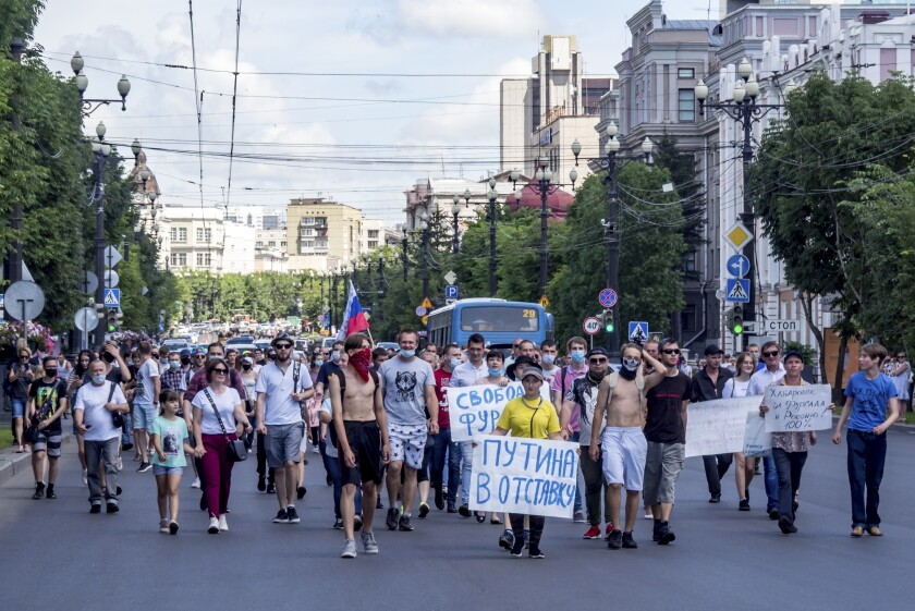 """People hold posters that read: """"Freedom for Sergei Furgal"""" and """"Putin to Resign!"""", during an unsanctioned protest in support of Sergei Furgal, the governor of the Khabarovsk region, in Khabarovsk, 6100 kilometers (3800 miles) east of Moscow, Russia, Sunday, July 12, 2020. Sergei Furgal was arrested Thursday and flown to Moscow where he was interrogated and ordered held in jail for two months. Russia's main criminal investigation body says he is suspected of involvement in several murders of businessmen in 2004 and 2005, before his political career began. (AP Photo/Igor Volkov)"""