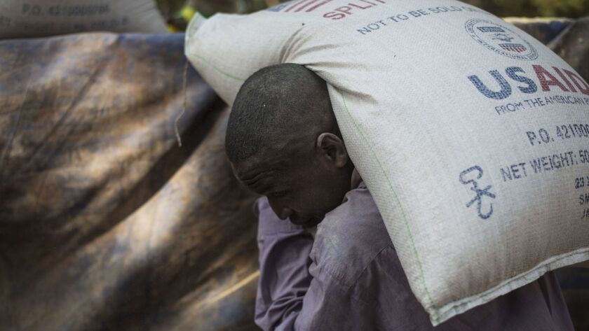 A man carries a bag of food delivered by the United States Agency for International Development to a