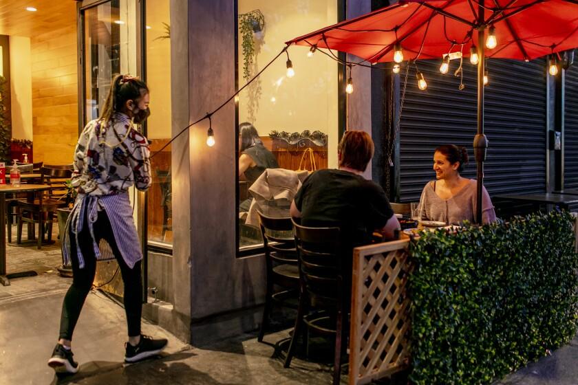 Los comensales se sientan en la mesa del patio de un restaurante.