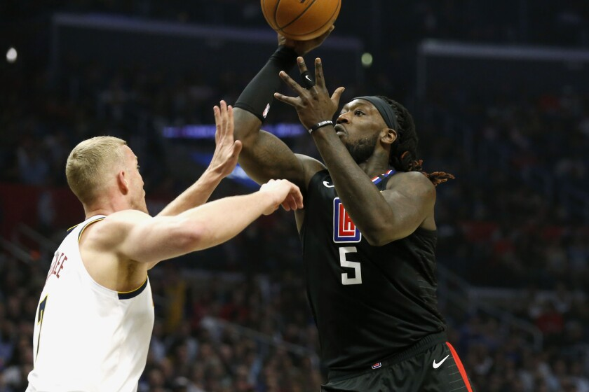 Clippers' Montrezl Harrell shoots over Denver Nuggets center Mason Plumlee on Feb. 28, 2020.
