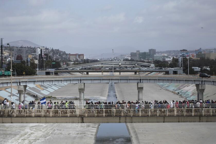 Central Americans walk toward the U.S. border in Tijuana to request asylum.