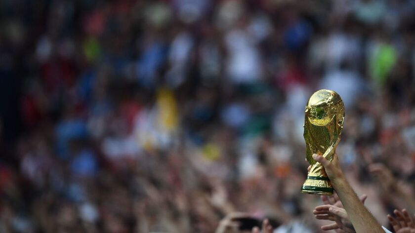 An England supporter carries a replica of the World Cup trophy during the World Cup semifinal between Croatia and England at the Luzhniki Stadium in Moscow.