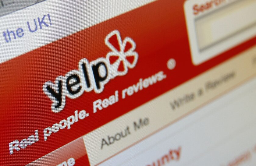 This 2010 file photo shows the Yelp website on a screen in Los Angeles. New York City health officials found three unreported outbreaks of food poisoning by sifting through hundreds of thousands of comments on the popular website, according to a report released May 22, 2014.