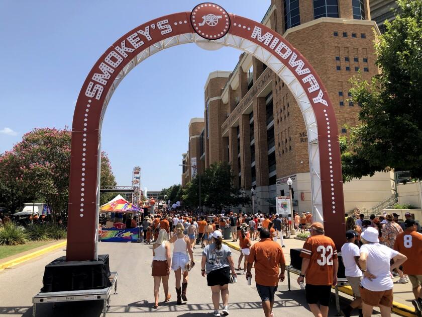 Texas Longhorns fans walk under an arch on a street