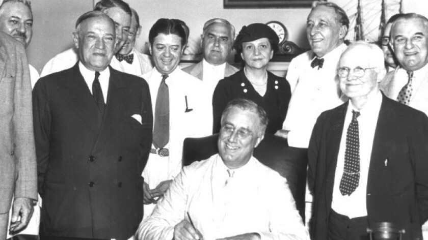 Happy birthday: President Franklin D. Roosevelt signs the Social Security Act on August 14, 1935. Directly behind him: Secretary of Labor Frances Perkins, who ushered the act into being.
