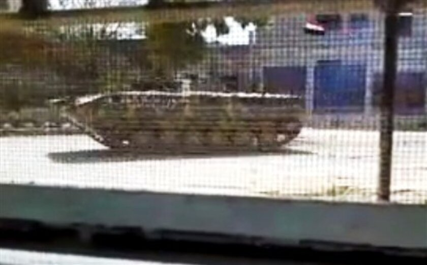 In this image made from amateur video released by the Shaam News Network and accessed Thursday, April 12, 2012, purports to show a Syrian military armored vehicle in Idlib, Syria. Syrian forces halted attacks on opposition strongholds Thursday in line with a U.N.-brokered truce but the regime defied demands by international envoy Kofi Annan to pull troops back to their barracks, activists said. (AP Photo/Shaam News Network via AP video) TV OUT, THE ASSOCIATED PRESS CANNOT INDEPENDENTLY VERIFY THE CONTENT, DATE, LOCATION OR AUTHENTICITY OF THIS MATERIAL