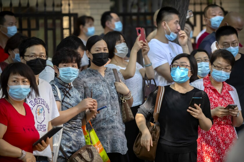 Relatives wearing face masks to protect against the new coronavirus watch as students line up for the first day of China's national college entrance examinations, known as the gaokao, in Beijing, Tuesday, July 7, 2020. China's college entrance exams began in Beijing on Tuesday after being delayed by a month due to the coronavirus outbreak. (AP Photo/Mark Schiefelbein)