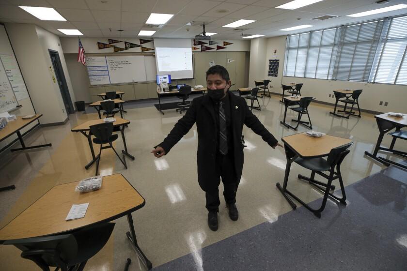 A teacher stands inside an empty classroom.