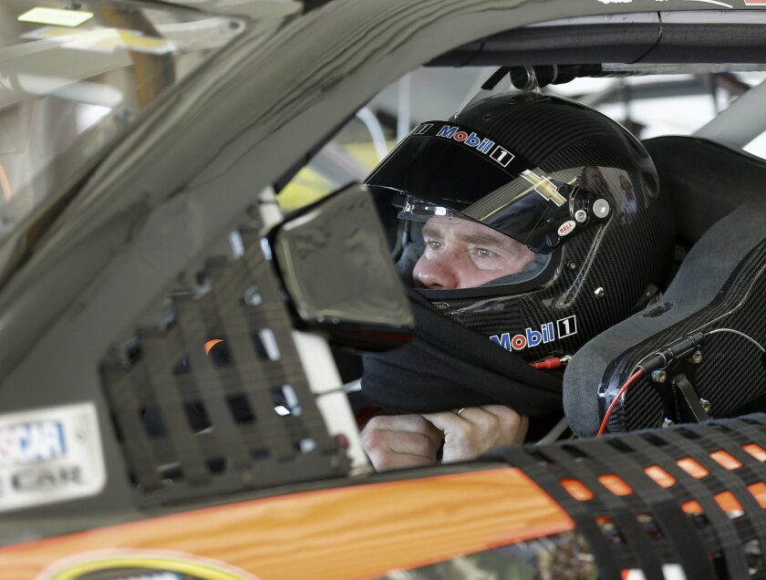Brian Vickers adjusts his helmet before leaving his garage during a practice session for the NASCAR Daytona 500 auto race at Daytona International Speedway, Saturday, Feb. 13, 2016, in Daytona Beach, Fla. (AP Photo/John Raoux)