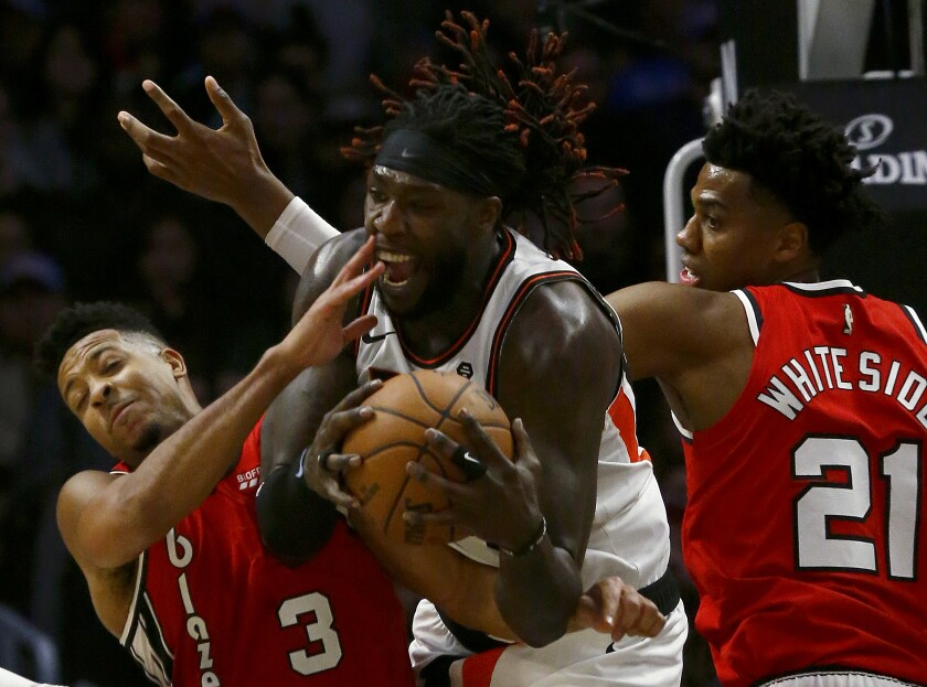 Clippers forward Montrezl Harrell pulls down a rebound between Portland Trail Blazers' CJ McCollum, left, and Hassan Whiteside in the fourth quarter at Staples Center on Tuesday.