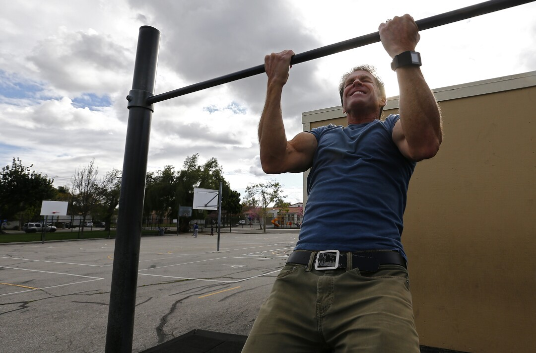 Mike Lynn works out on playground equipment at Longfellow Elementary School in Long Beach.