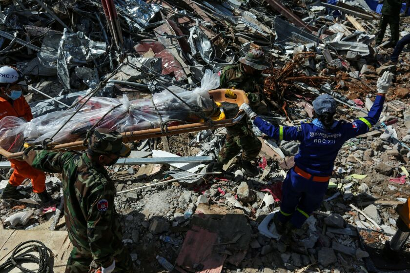 Rescue workers recover the body of a victim from the debris of an under-construction building two days after it collapsed in Sihanoukville early on June 24, 2019. - The retrieval of bodies from a building collapse in Cambodia continued on June 24, as the death toll rose to 24 with no further survivors expected to be found under the debris of the seven-storey Chinese-owned construction site.