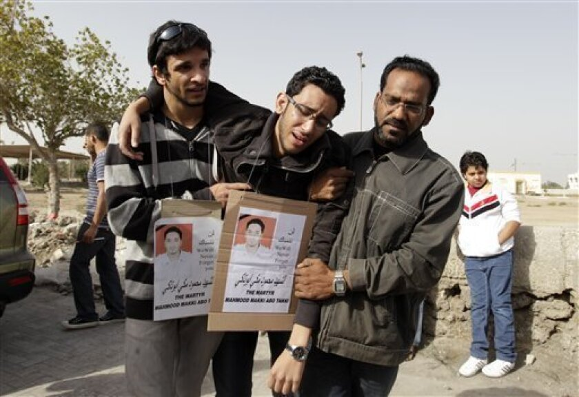 Friends of Mahmoud Maki Abu Taki, 22, who died during clashes between Bahraini anti- government protesters and riot police on early Thursday, cry during his funeral procession in Sitra village, Bahrain, Friday, Feb. 18, 2011. (AP Photo/Hassan Ammar)