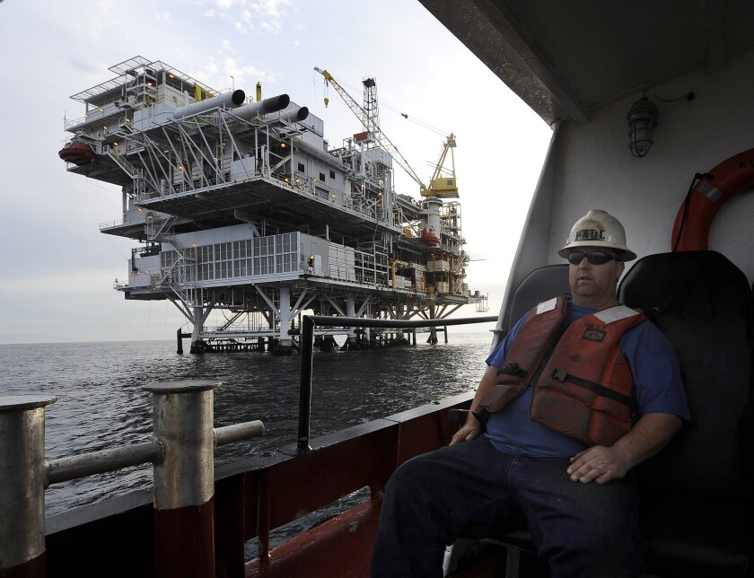 A worker in a hard hat arrives by boat at an offshore oil drilling platform.