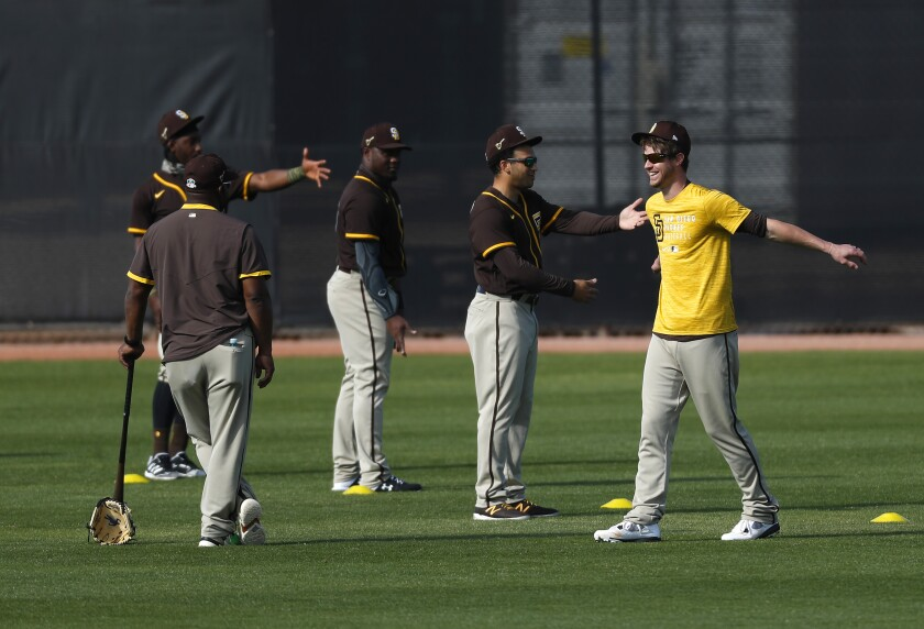 Padres outfielders stretch at the start of a spring training workout.