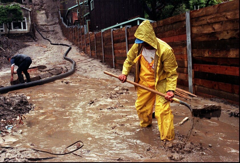In this Wednesday, March 25, 1998 file photo, Enrique Lagunas digs a trench to redirect water toward a street in Laguna Beach after heavy rains from an El Nino storm hit Southern California. (AP Photo/Orange County Register, Bruce Chambers)