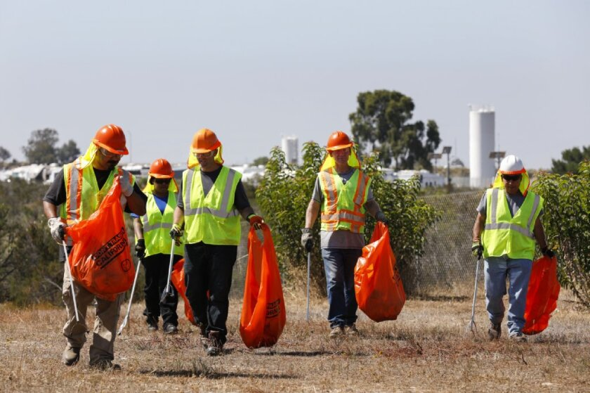 A Caltrans crews hired through the Back2Work program clears trash alongside Interstate 15 near Miramar Way on Tuesday morning. In San Diego County, Back2Work finds work for veterans who have experienced homelessness. Caltrans recently has more than doubled the number of people it hires through the program.
