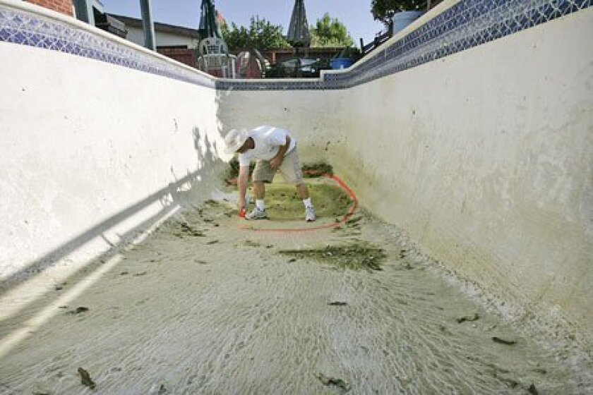 """Bill Stults of James Construction Cleanup Inc. marked where drainage holes could be punched into a pool being demolished in La Mesa. """"I'm getting calls all of the time, sometimes three or four a day,"""" Stults said. (John Gibbins / Union-Tribune)"""