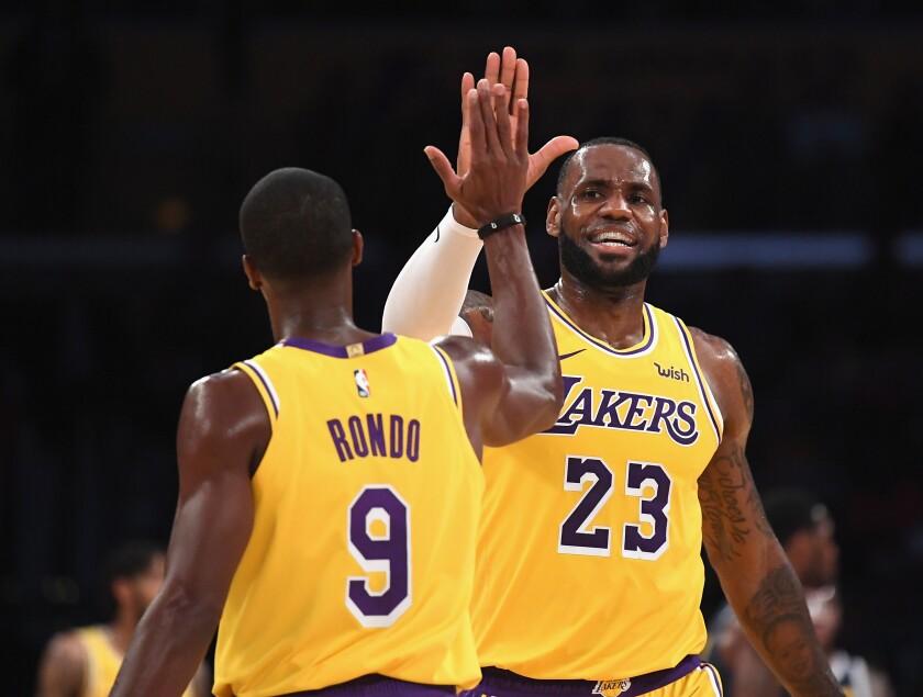 Lakers point guard Rajon Rondo and forward LeBron James celebrate during a game last season.