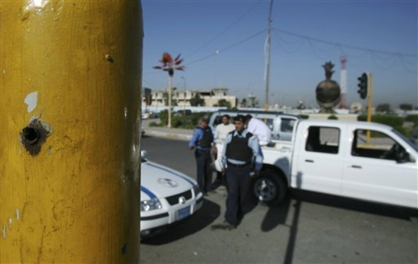 A bullet hole is seen on a traffic light pole at al-Nisoor square in Baghdad, Iraq, Sunday, Dec. 7, 2008. At this square, more than a year ago, Blackwater Worldwide security guards shot dead 17 Iraqi civilians. The US Justice Department has indicted five Blackwater Worldwide security guards and is negotiating a plea deal with a sixth, according to people close to the case.The six guards have been under investigation since a convoy of heavily armed Blackwater contractors opened fire in a crowded Baghdad intersection on Sept. 16, 2007. (AP Photo/Hadi Mizban)
