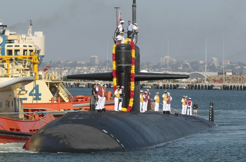 The USS La Jolla, a Los Angeles-class fast attack submarine, comes into dock at Naval Base Point Loma in San Diego for a welcoming ceremony on Tuesday. This is the La Jolla's final visit to San Diego before decommissioning later this year.