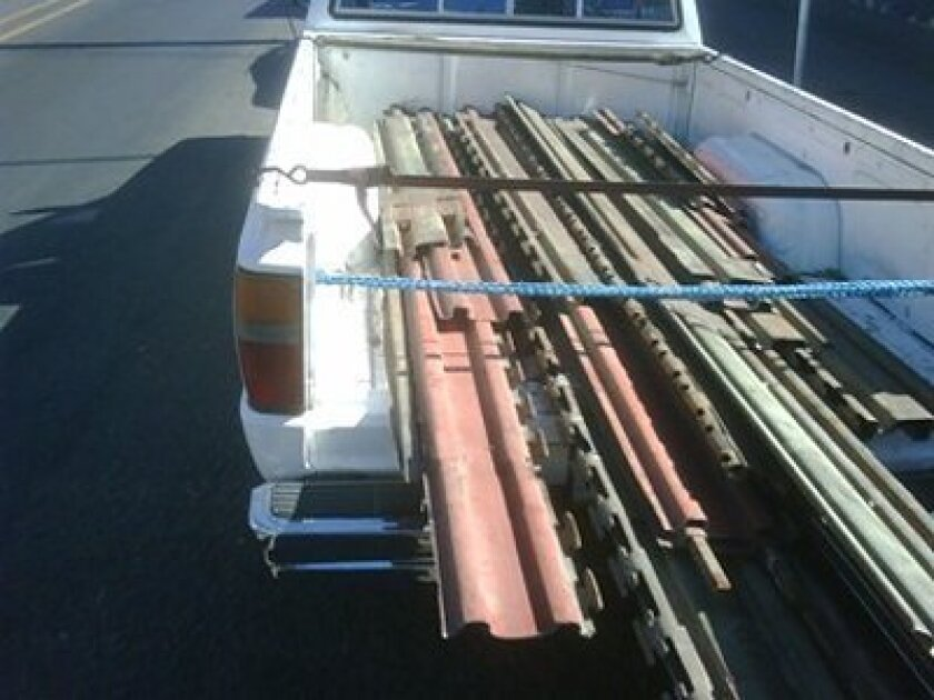 Pieces of the U.S. border fence are seen in the back of a pickup truck in this photo from the Tijuana Police Department.