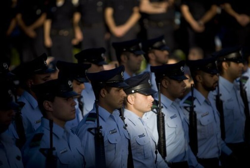 Israeli police honor guard stand at attention.