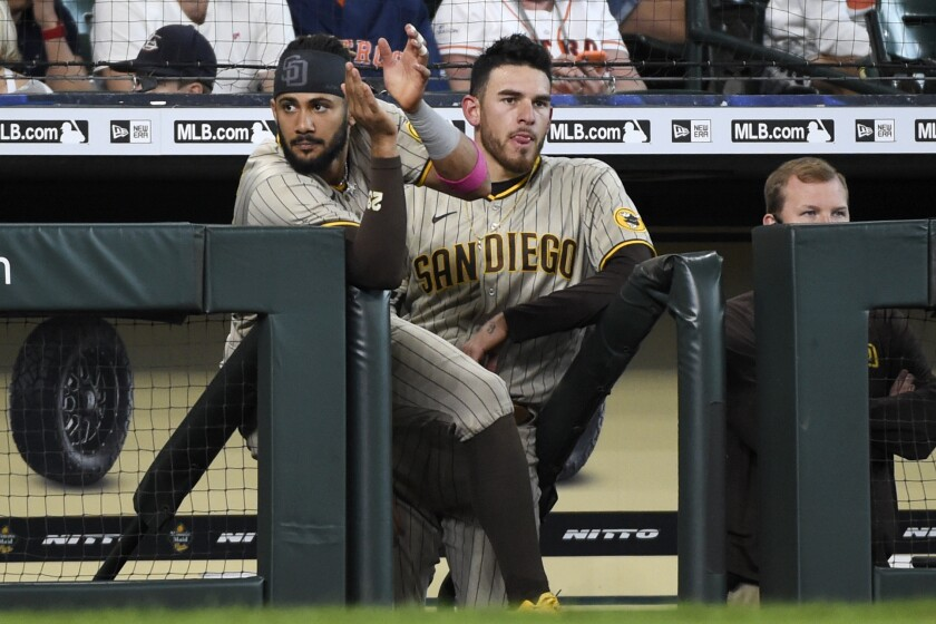 Fernando Tatis Jr., left, and Joe Musgrove watch from the dugout during the ninth inning of Sunday's game against the Astros.