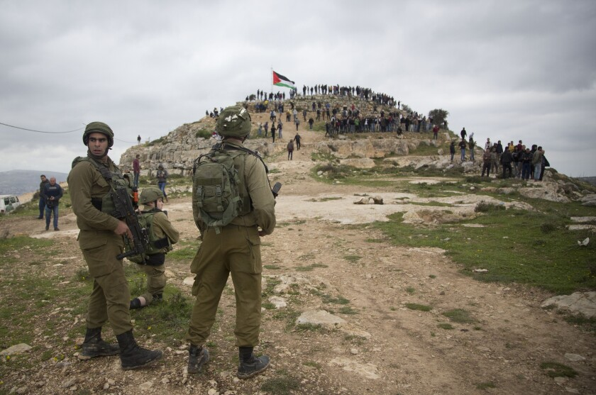 Israeli soldiers, foreground, monitor a crowd on a hilltop bearing a Palestinian flag