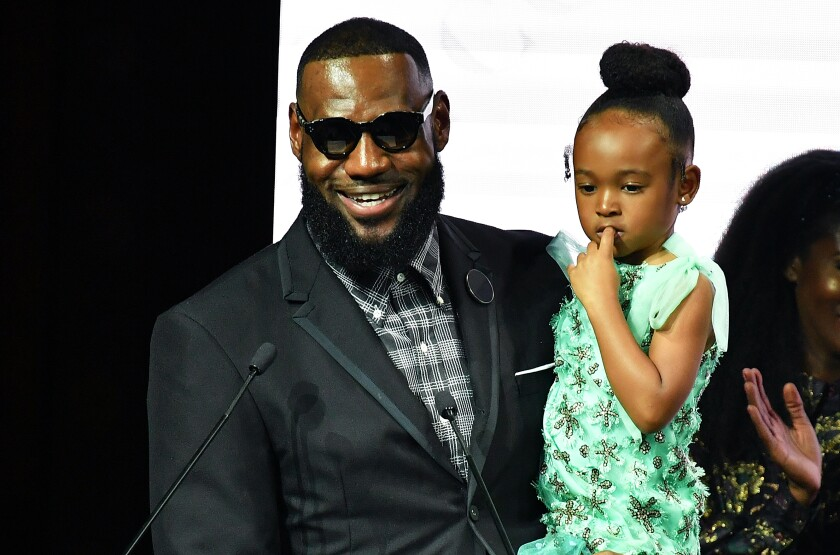 LeBron James holds his daughter Zhuri while attending an event at Harlem's Fashion Row.