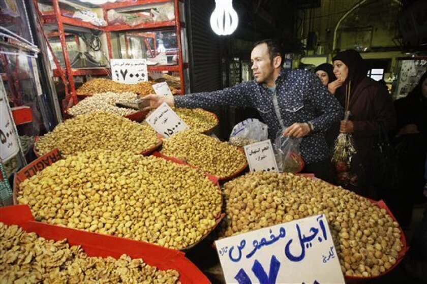 In this Thursday, Feb. 2, 2012 photo, an Iranian vendor sells pistachio in Tehran's old main bazaar, Iran. A simple trip the store these days offers a crash course in life under sanctions. The price tags on many imported goods from South Korean refrigerators to Turkish crackers are sometimes double from last year. The money to buy them, meanwhile, has plunged in value against the U.S. dollar and other foreign currencies. (AP Photo/Vahid Salemi)