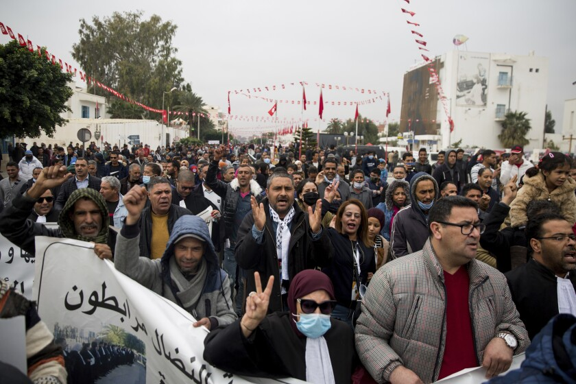 People march and shout slogans as they attend a protest in Sidi Bouzid, Tunisia.